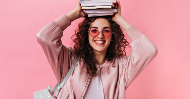 Teenage girl in pink outfit posing with books